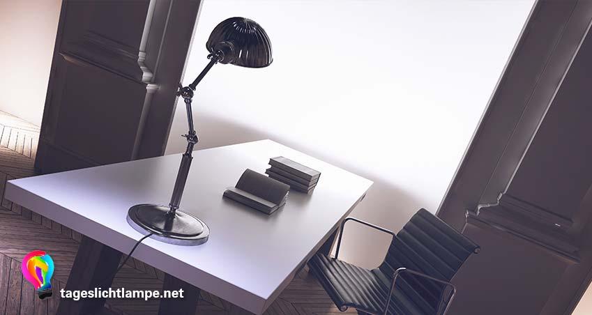 Tageslichtlampe auf Schreibtisch. Auf dem Schriebtisch liegen Bücher. Im Hintergrud ist ein offenes helles Fenster zu sehen