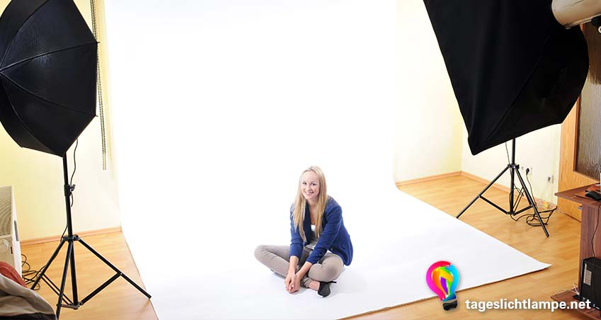 Einsatz einer Tageslcihtlampe im Fotostudio. Zu sehen sind links und rechts im Bild jeweils zwei Standlampen, die eine junge Frau ausleuchten, die auf einem weißen Hintergrund auf dem Boden sitzt.