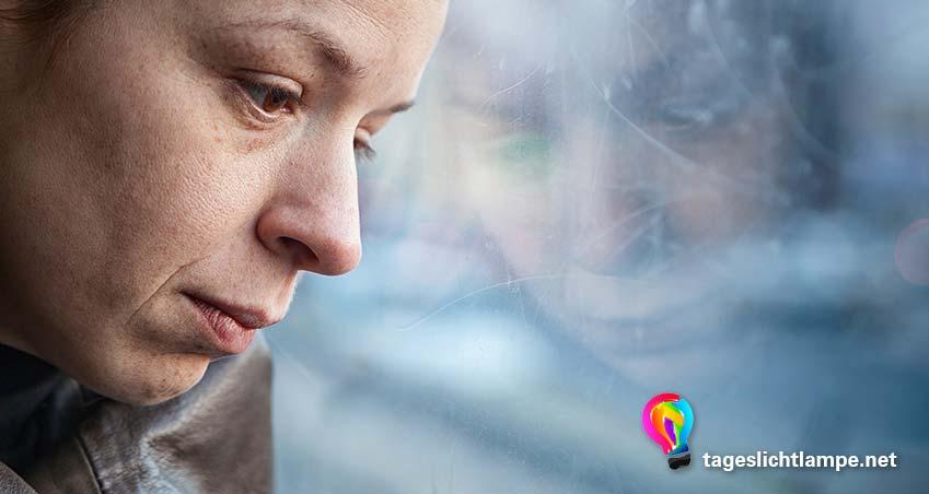 EIne depressive Frau sitzt am Fenster und guckt traurig - bei Depressionen hilft oft eine Tageslichtlampen Lichttherapie