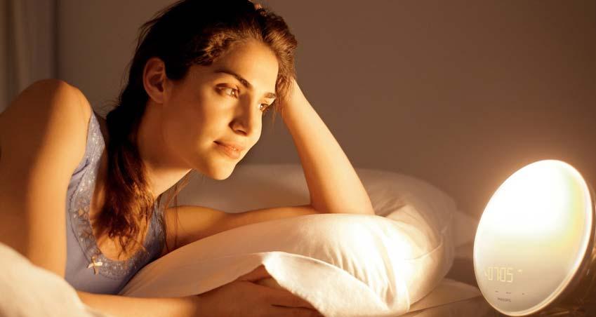 Frau liegt im Bett und schaut auf Tageslichtwecker von Philips auf dem Nachttisch