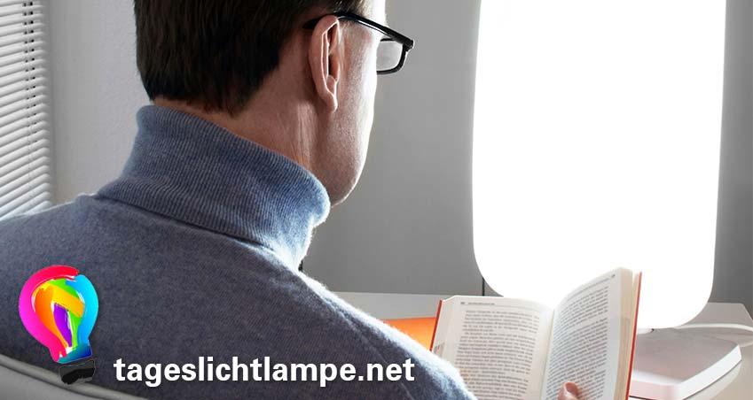 Tageslichtlampe im Einsatz - Mann sitzt mit Buch vor einer Tageslichtlampe