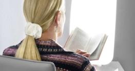Blonde Frau vor einer Tageslichtlampe liest ein Buch