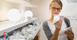 Frau vor Lampenregal um eine Tageslichtlampe zu kaufen. Dabei hält sie ein Tageslicht Leuchtmittel in der Hand und liest die Verpackungstexte