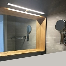 Wandspiegel mit Holzrahmen. Darüber eine Tageslichtlampe für Bad.