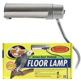 Tageslichtlampe Vögel, eine vertikale silberne Lampe über einer gelben Verpackung mit Vogelmotiv