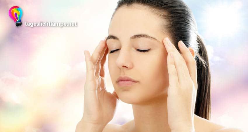 Frau mit Migräne nutzt eine Sonnenlicht Lampe zur Tageslichttherapie