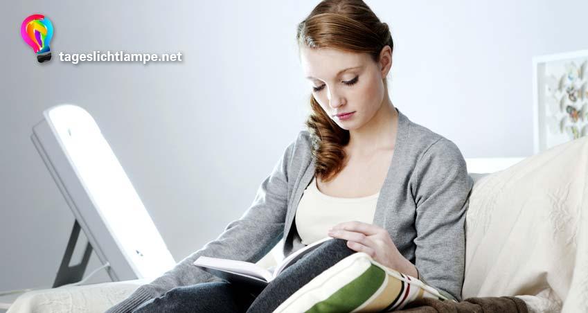 Frau nutzt eine Sonnenlicht Lampe zum lesen