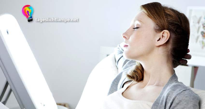 rotherige Frau mit geschlossenen Augen vor einer Sonnenlicht Lampe um Ihre Stimmung zu verbessern